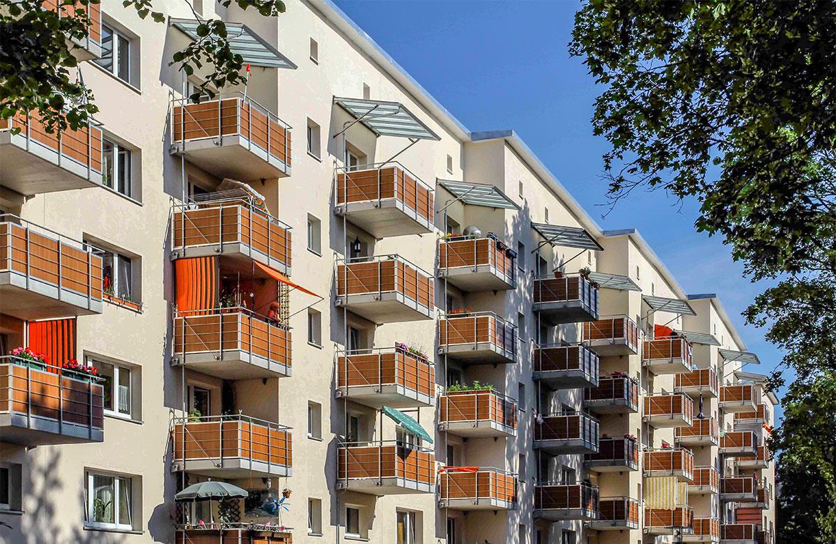 Abgehängte Betonbalkone mit Stahl-Trespa-Geländer in Holzoptik